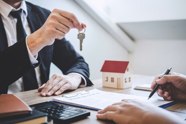 En mäklare räcker över nyckeln till en bostad till en man som sitter tvärs över bordet med ett kontrakt framför sig och en penna i handen.