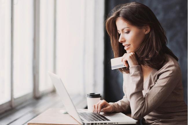 Kvinna tittar på laptop och håller höger hand på tangentbordet. I vänster hand håller hon i ett kreditkort.