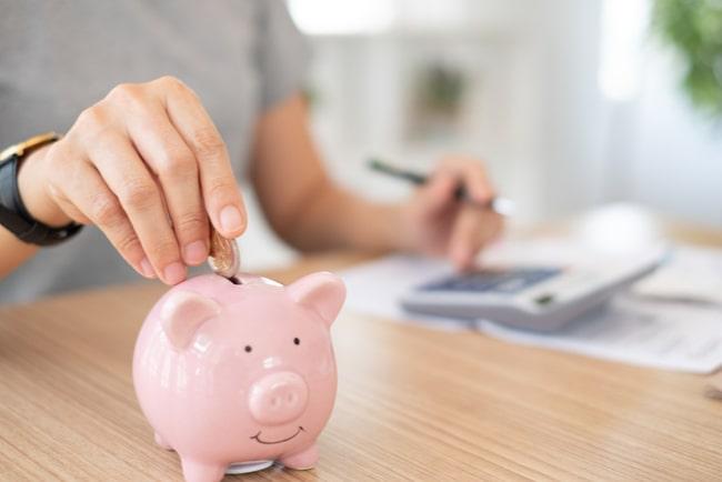Kvinna stoppar pengar i en rosa spargris samtidigt som hon räknar på en miniräknare och gör anteckningar.
